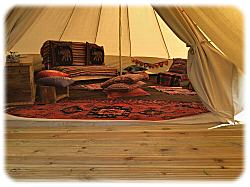 inside bell tent with futon seats and carpet